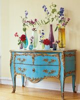 Various vases of flowers on blue chest of drawers