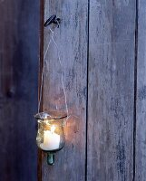A glass lantern with a burning candle hanging on a wooden wall