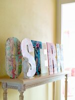 The word 'Ostern' (German: Easter) in decorative letters on a console table