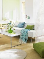 A light-flooded, white living room with a sofa, coffee table and touches of green and blue