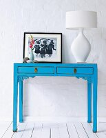 A white table lamp and a photograph on a blue console table against a white, plastered stone wall
