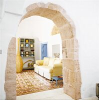 A view through an archway made of limestone blocks into a living room with a tiled floor