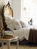 Romantic bedroom with bed, pillow, white bed linen and ornate chair