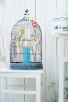 Candle in cage decorated with paper flowers and birds on outside