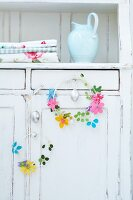Easter wreaths of wire and felt flowers on door of old cupboard