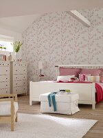 White double bed and chests of drawers in bedroom with pink and white floral wallpaper and ceiling beam