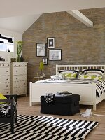 White double bed and chests of drawers in bedroom with stone-effect wallpaper, black and white rug and roof beam