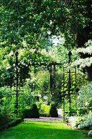 A rose arch and obelisks in a resplendent garden