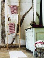 Vintage bathroom with wooden ladder as towel rack
