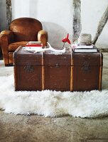 An old wooden chest being used as a coffee table on a white flock rug with a brown leather armchair in the background against a half-timbered wall