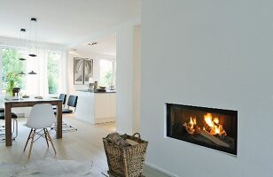 Basket in front of fireplace in open-plan interior with white walls