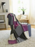 A knitted checked woollen blanket hanging over an armchair