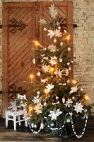 A Christmas tree in front of a rustic wooden door decorated with nostalgic paper stars and candles