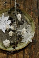 Christmas arrangement with paper snowflakes, baubles and larch cones