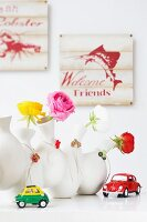 Roses in white vases with small pendants behind toy cars
