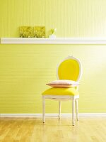 Cushion on chair against wall with green wallpaper and stucco dado rail used as shelf