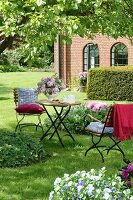 Fontenay table and chairs (by Garpa) below apple tree; house in background