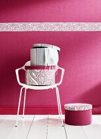 Hatboxes on white chair against deep pink wall