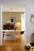 A view into a dining room with an oval table, chairs and a modern pendant lamp