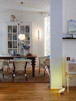 Blick in offenen Wohnraum mit Esstisch, Korbstühlen & Vitrinenschrank
