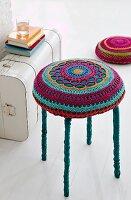 Colourful crocheted cushion on stool