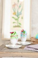 Colourful Easter eggs in egg cups decorated with daisies and ribbons