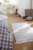 A white knitted rug on wooden floor boards in a bedroom