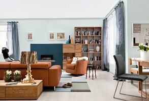 Open-plan living area with brown leather sofa set, shelving and fireplace