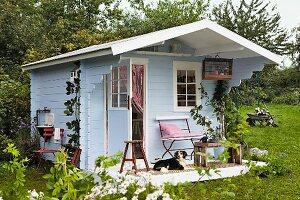Blue, wooden, Scandinavian-style summer house used as artist's studio