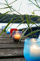 Tealight holders of various colours on lakeside jetty