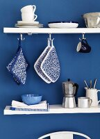 Kitchen utensils on white shelves on blue wall