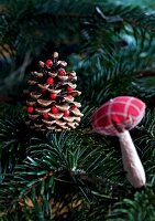 A pine cone and a fabric mushrooms on a Christmas tree