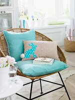 Decorative cushions, one with an Easter bunny motif on a wicker chair