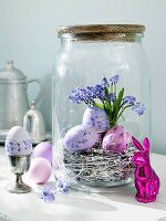 Purple Easter eggs in a preserving jar with an Easter bunny in front of it