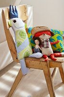 Cushions and stuffed dolls on a wooden chair