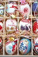 Colourfully painted Easter eggs in a seedling tray lined with straw