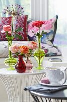 Roses in various glass vases on a side table