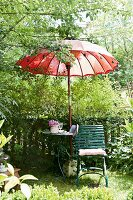 Seating area in summery garden with garden chair, garden table & red Thai-style parasol