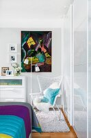 Reading corner in bedroom with wire armchair, standard lamp & artwork on wall