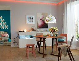 Esszimmer mit rundem Esstisch, Lichtleiste & beleuchtetem Sideboard