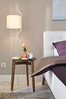 A pendant lamp in a bedroom hanging above a bedside table