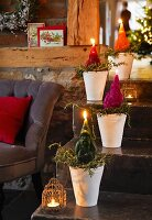 Father Christmas candles in flower pots on a flight of stairs