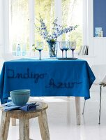 A table with an azure blue, embroidered table cloth