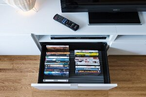 A collection of DVDs in an open drawer in a media unit with a television and a remote control