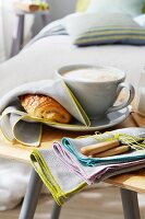 Pain au chocolat covered with a fabric napkin next to a cappuccino with a bundle of napkins on a wooden chair in front of a bed