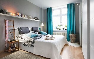 A bedroom with light-grey walls and blue curtains with a long bookshelf over a double bed