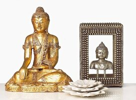 Decorative Metallic Buddahs and a Marble Lotus Flower on White Table