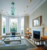 Traditional living room with bay window, green glass chandelier above sofas and fireplace