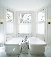 Vintage bathtubs with tap fittings in marble block in spacious, traditional bathroom with bay window
