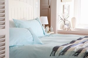 Double bed with light blue pillows and bedspread near a window